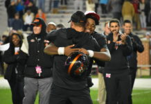 Hoover QB Jalen Parker and head coach Josh Niblett embrace following the Bucs' 48-20 win. (Aaron Daniel/JoxPreps)